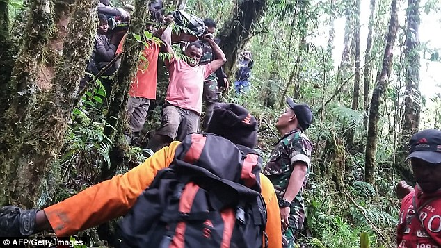 Search and rescue teams had to walk two hours to reach the crash site that was in a heavily forested area on a mountain side in the Oksibil subdistrict Sunday morning