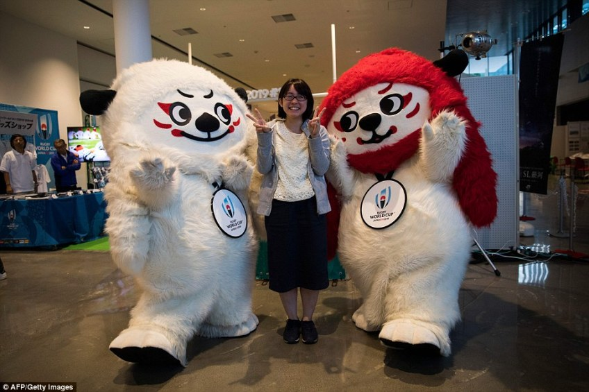 A Japanese woman poses with Rugby World Cup 2019 mascots, Ren (left) and G at a rugby pop-up museum in Kamaishi