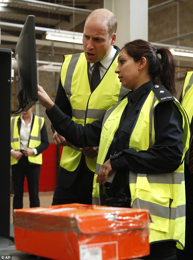 Prince William watches as a UK Border Force officer scans via an X-Ray machine incoming mail and parcels, to the United Kingdom, for contraband goods during a visit to the Royal Mail international distribution centre near Heathrow airport