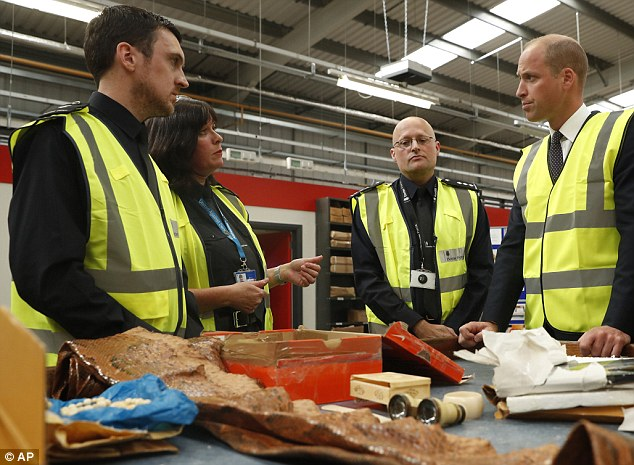 Prince William watches as a UK Border Force shows off various items found recently, including snake skin, ivory and plants that are not allowed into Britain