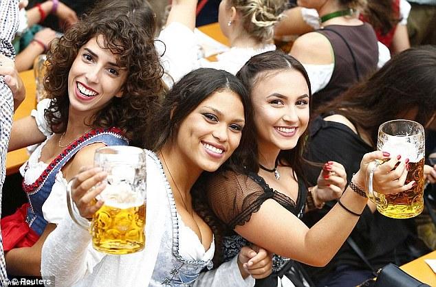 Un groupe de trois filles sourient alors qu'elles brandissent leurs grands verres de bière lors de la fête de l'an dernier