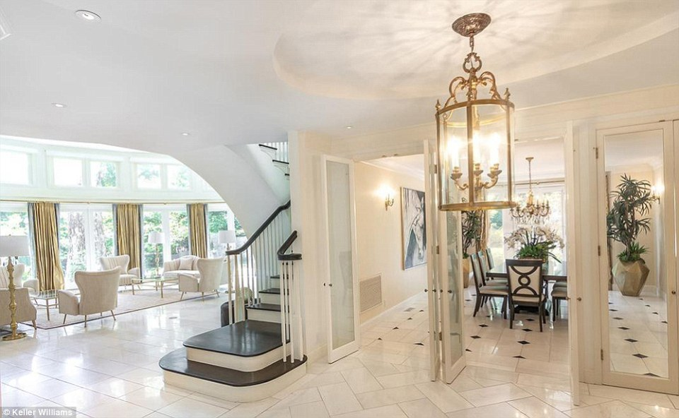 The entryway opens on to the dining room and a narrow but sweeping staircase to the upper level, which features a total of six bedrooms and seven bathrooms