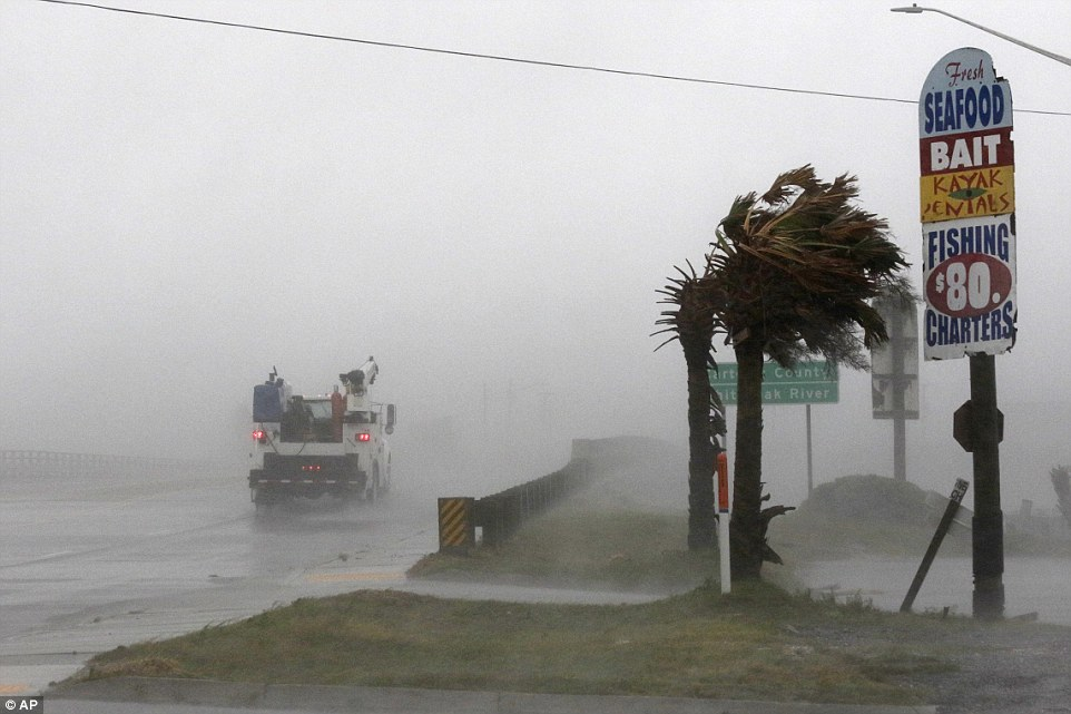 A work truck drives on Hwy 24 as the wind from Hurricane Florence blows palm trees in Swansboro on Thursday