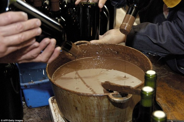 Workers seal the bottles of wine with hot wax. The subterranean wine kingdom was formerly a limestone mine that was converted into the huge wine cellar in the 1960s