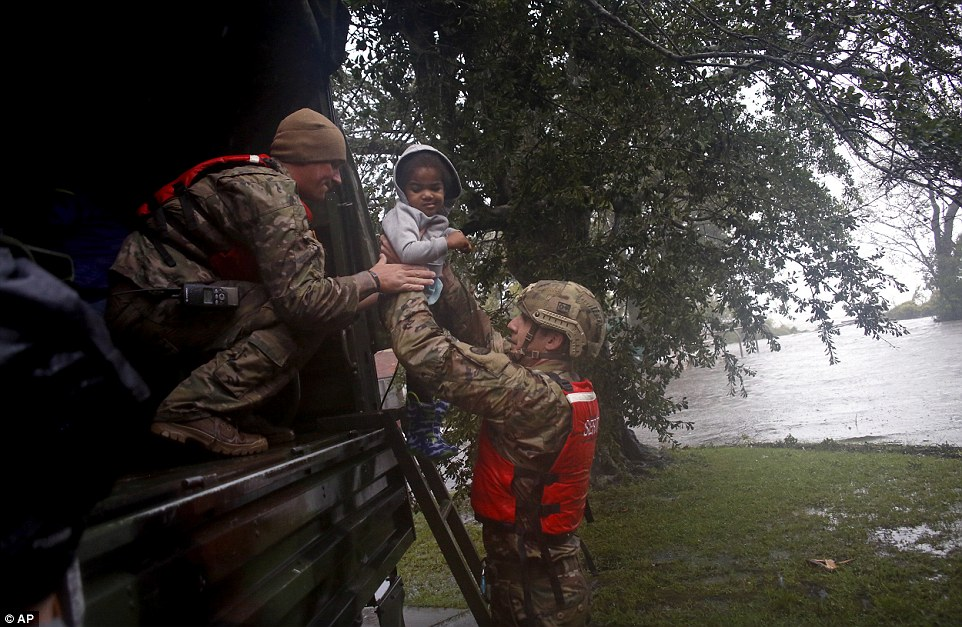 Rescue team members Sgt. Matt Locke (left) and Sgt. Nick Muhar (right)  evacuates a family from floodwaters in New Bern