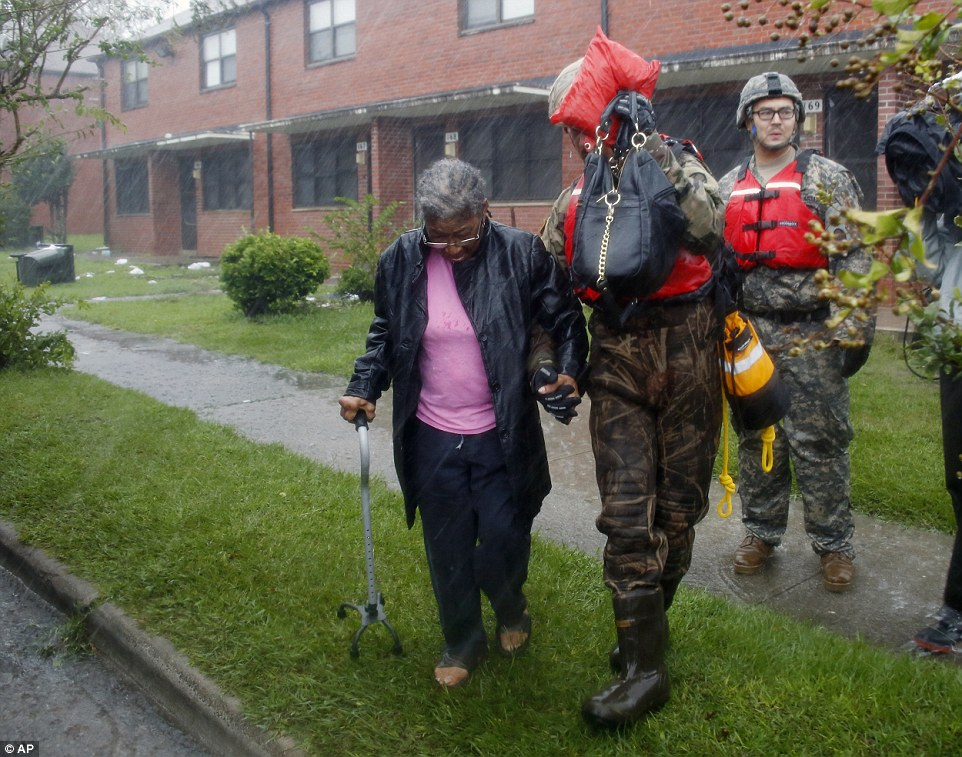 A rescue team from the North Carolina National Guard 1/120th battalion evacuates an elderly woman from her apartment as the rising floodwaters from Hurricane Florence threatens her home in New Bern on Friday