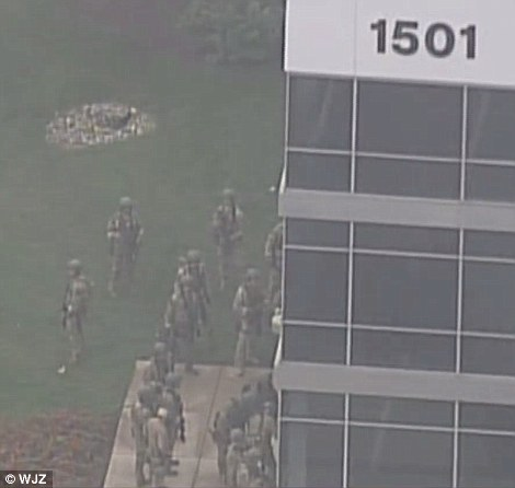 A tactical response team is pictured arriving at the Rite Aid building where three were killed and at least two were injured