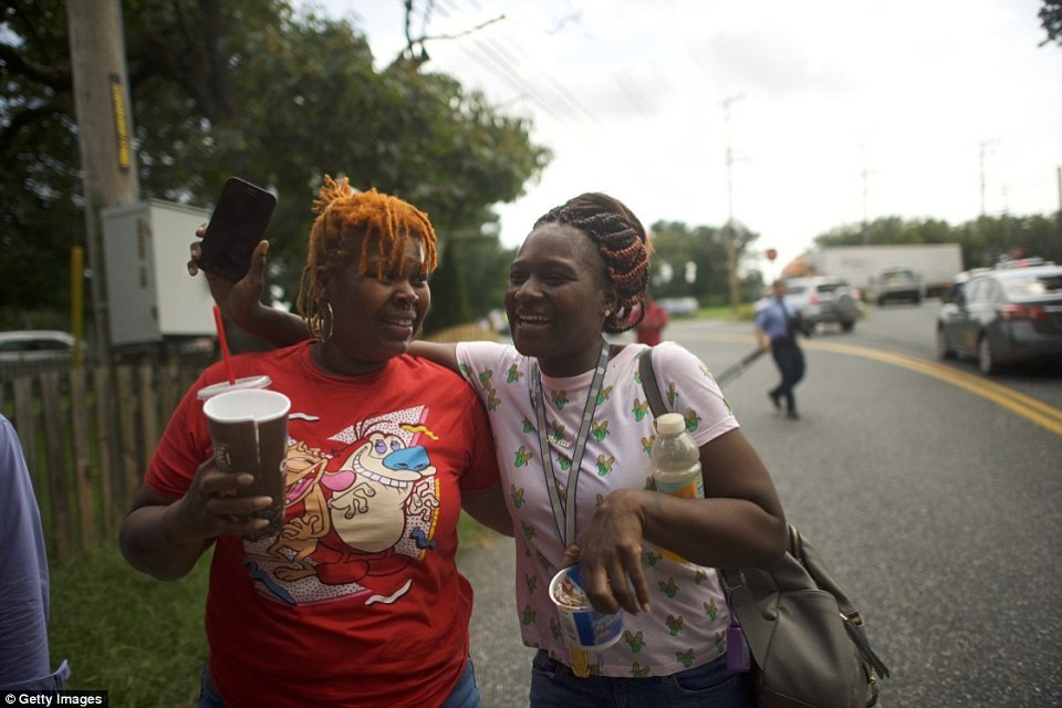 Two women embrace after leaving the business park where the shooting happened on Thursday morning