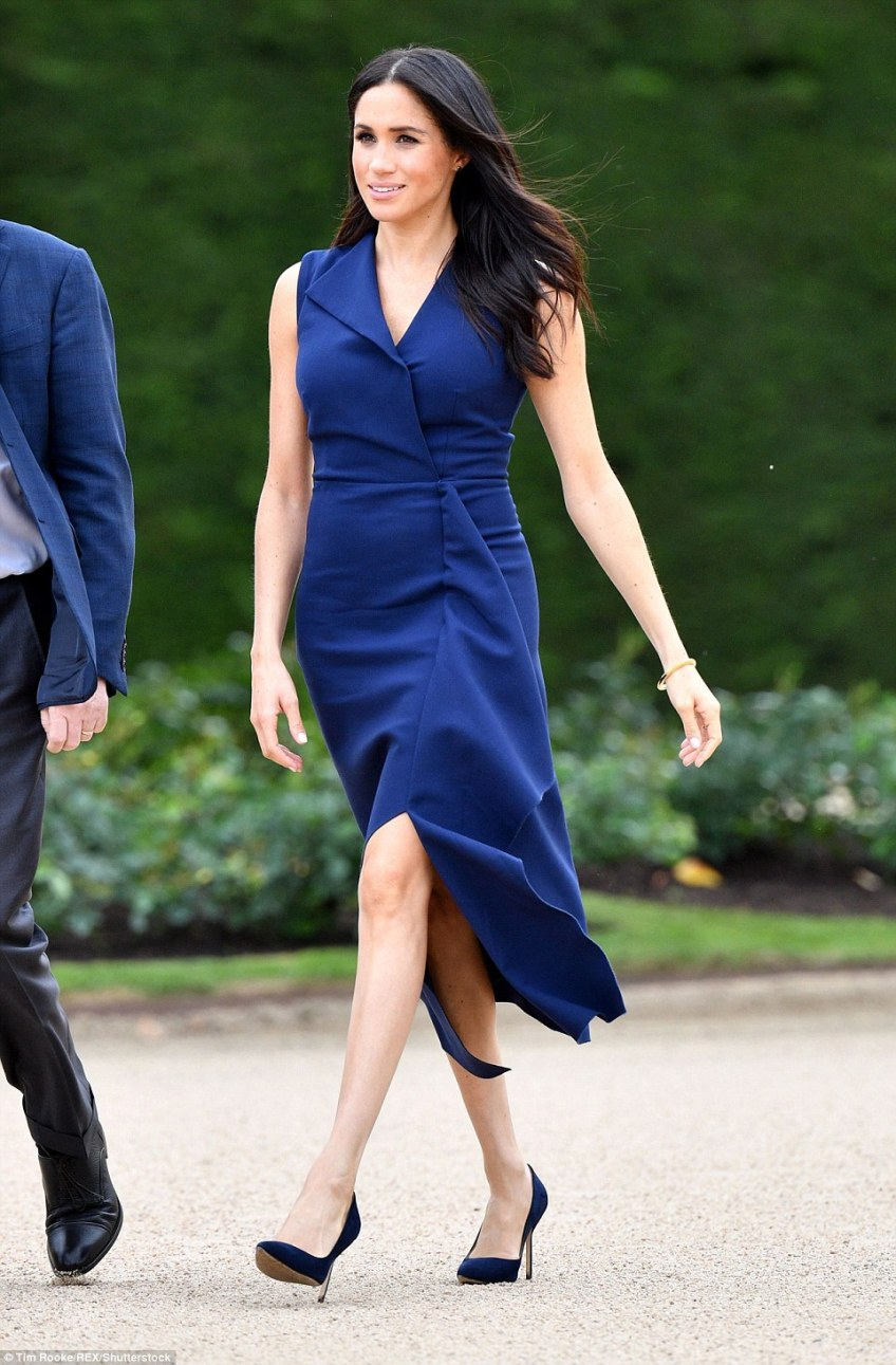 Recently announced pregnant, Meghan removed her coat as the couple approached the steps of Government House
