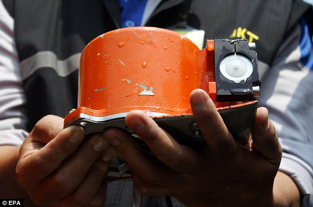 An Indonesian officer holds the Lion Air JT610 flight data recorder shortly after it was found underwater in November 2018
