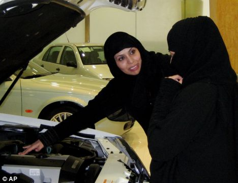 Saudi women look at a new car