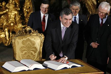 Gordon Brown smiles as he signs the Lisbon Treaty