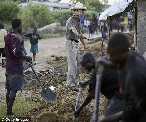 A Chinese supervisor cajoles local workers as they dig a trench in Kabwe, Zambia