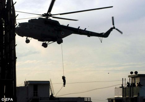 A National Security Guards commando ropes down from a helicopter onto the roof of Nariman House