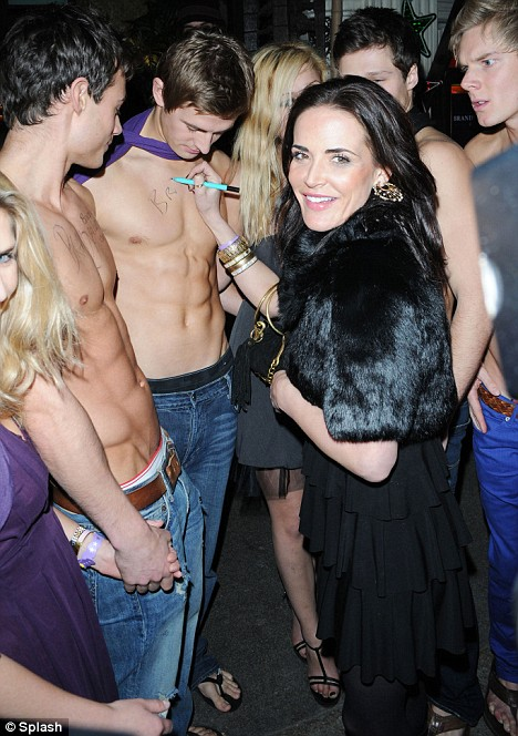 Sophie Anderton launched the Brandy Melville men's clothing line by writing its logo onto topless male models at the label's launch party in Mahiki