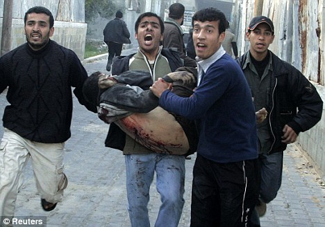 A wounded Palestinian is carried near a United Nations school in Jabalya after a bombing in which at least 40 people died, 7.01.09