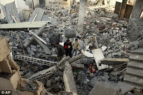 Palestinians inspect the rubble of a destroyed building in Rafah refugee camp, southern Gaza, 7.01.09