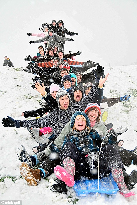 Thrills and spills: Teenagers slide conga-style down a hill in Rochester, Kent