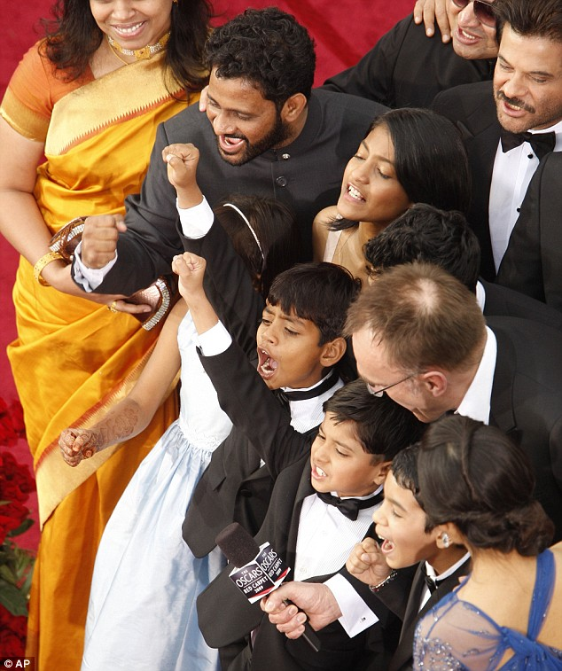A cheer for Hollywood: The cast of Slumdog Millionaire join director Danny Boyle, bottom right with glasses, on the red carpet