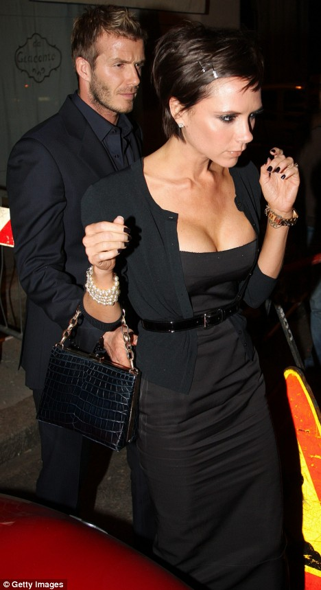 Busting out: Victoria Beckham displayed a voluptuous cleavage as she left a Milan restaurant with husband David last night