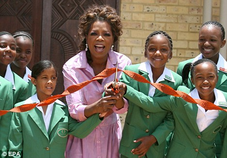 Oprah Winfrey (C) cuts the ribbon with some of the girls who have enrolled in her school during its opening in January 2007