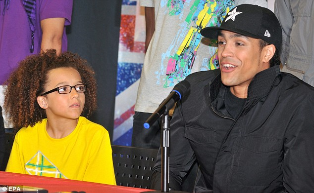 Keeping his feet on the ground: Diversity's lead dancer Ashley Banjo (R) and 13-year-old Perry Kiely at a press conference following their win