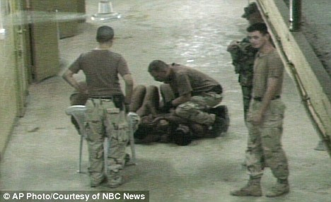 Disgrace: Iraq detainees appear to be surrounded by U.S. military personnel at the Abu Ghraib prison
