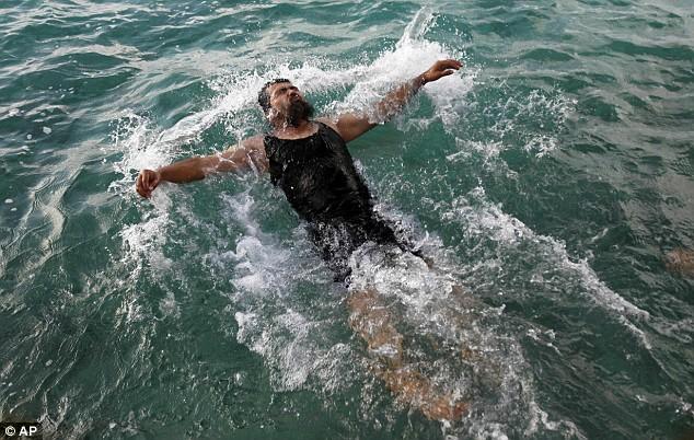Salahidin Abdulahat takes a dip in the Atlantic ocean off the shore near Hamilton