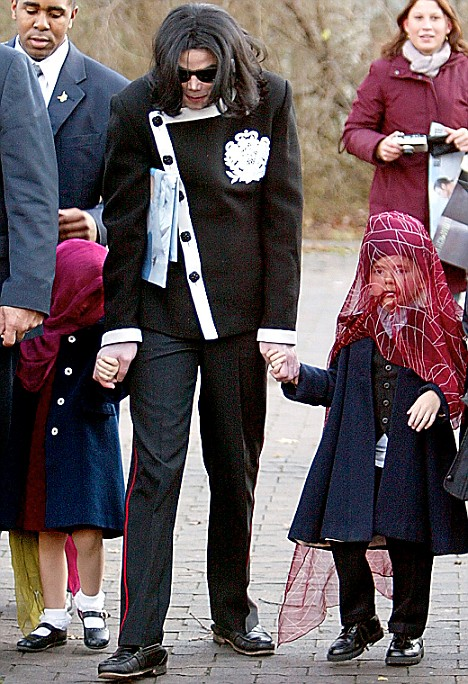 Jackson holds the hands of his two children Paris Michael, four, and son Prince Michael, five, in 2002. The children hated wearing the masks