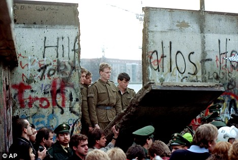 East German border guards look through a hole in the Berlin Wall after demonstrators pulled down the segment at Brandenburg Gate in Berlin
