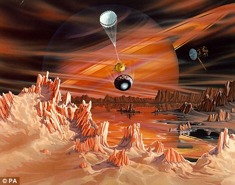 An artist's conception showing Titan's earth-like surface with Saturn appearing dimly in the background through the thick atmosphere