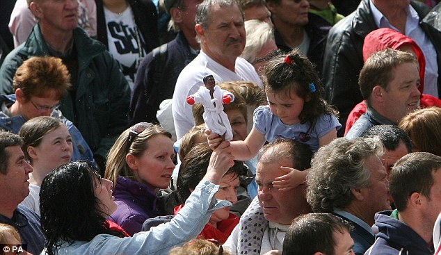 A young girl carries a doll of the boxing legend as she's surrounded by crowds who turned out to witness Ali's historic visit