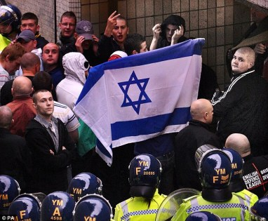 Sodden English Defense League demonstrators wave the Israeli flag (Daily Mail)