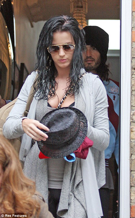 Brand new romance: Katy is snapped leaving Russell Brand's flat on Saturday morning, as the comic carries her suitcase just behind her