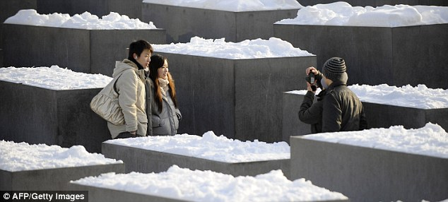 Tourists photograph each other beside the snow-covered concrete steles at the Memorial for the Murdered Jews of Europe in Berlin