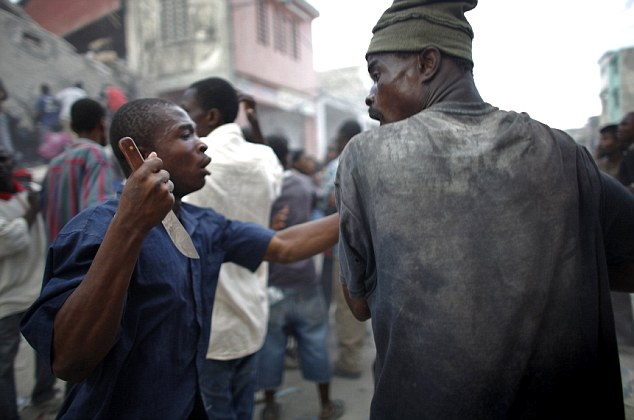 A looter holds a knife as he fights for products after Tuesday's earthquake in Port-au-Prince January 16, 2010