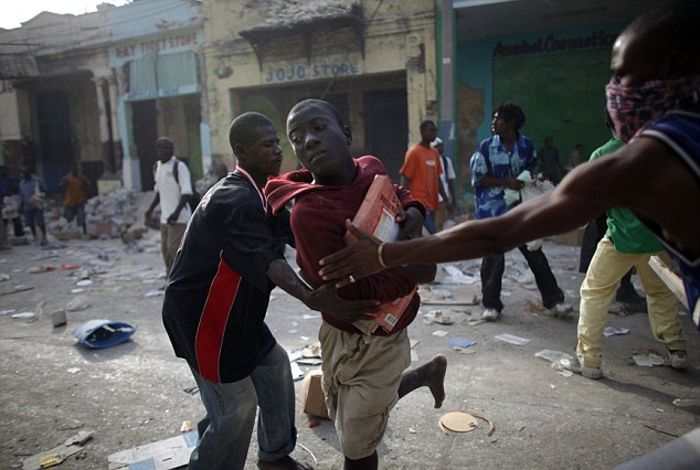 Looters fight for products at a business area in Port-au-Prince