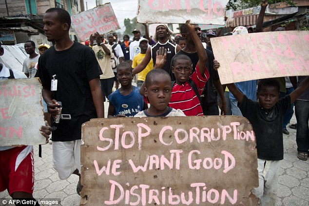 Children hold up placards demanding help in Leogane, one of the towns worst hit by the earthquake