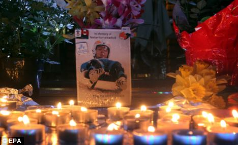 Shrine: Flowers and candles surround a photo of the Georgian luger Nodar Kumaritashvili