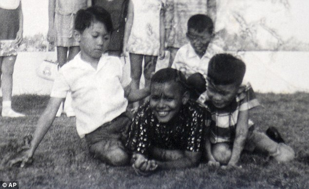 Chubby: Barack Obama, then known as Barry Soetoro, centre, is pictured at a classmate's birthday party in Jakarta, Indonesia, in 1971