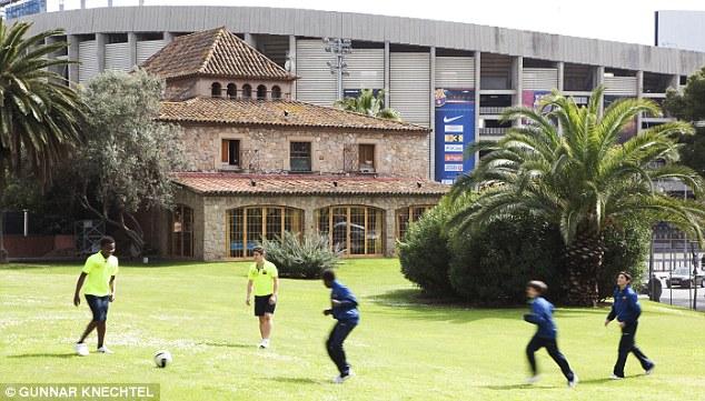 Para pemain muda FC Barcelona sedang bermain di halaman rumpu La Masia, dengan latar belakang stadion legendaris Barcelona : Nou Camp