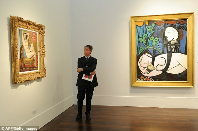 A prospective buyer admires Matisse's 'Nu au coussin bleu' as Picasso's piece hangs alongside it prior to the auction