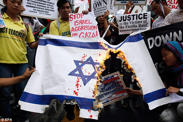 World condemnation: An Israeli flag burns outside the embassy in Manila in the Philipines today as global anger over the attack on the Gaza aid convoy increased