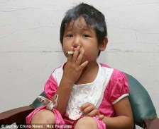 Addicted: Three-year-old Ya Wen smokes a cigarette. She took up the vice after being hit by a van in Huizhou, China