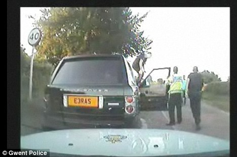 One policeman climbs onto the bonnet. Two officers had been removed from operational duty