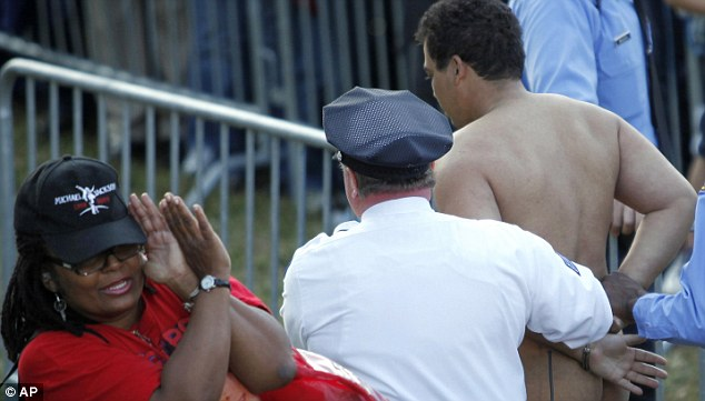 Er - what? A woman recoils as a naked man is escorted from Mr Obama's rally in Philadelphia today. It is not clear if the man was involved in the book-throwing incident - or why he was not wearing clothes
