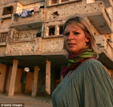 Booth stands next to a damaged building in Gaza in 2008