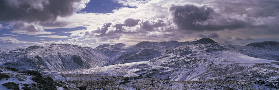 Touching the void: Dale Head in the Lake District reaches up towards the clouds on a winter's evening, with Scafell Pike, England's tallest mountain, looming in the distance
