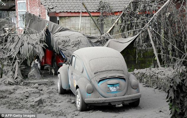 Blanketed: A VW Beetle is covered in the village of Muntilan, where many fatalities have been recorded