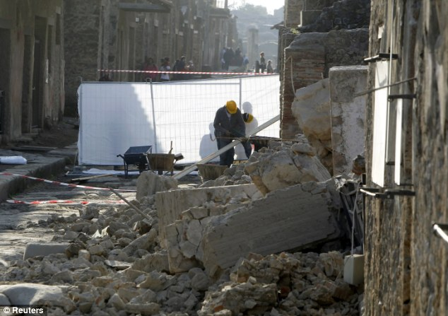 Relic from the past: Workers inspect the damage at the collapsed 'House of the Gladiators'. The public are not allowed to walk around the ruins but are able to view them from outside along one of the ancient city's main streets